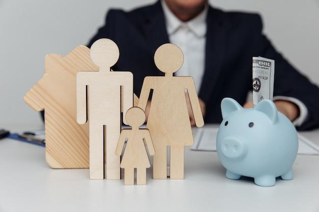 Homem por trás de figuras de família jovem e cofrinho com compra em dinheiro ou conceito de hipoteca