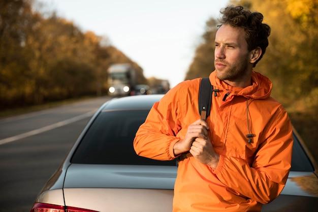 Homem posando ao lado de um carro durante uma viagem