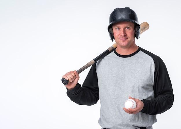 Homem posando com bola e chapéu de beisebol