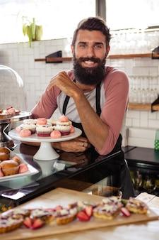 Homem posando com bolos