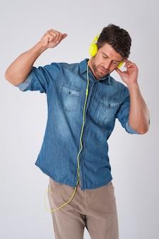 Homem posando com camisa jeans e fones de ouvido