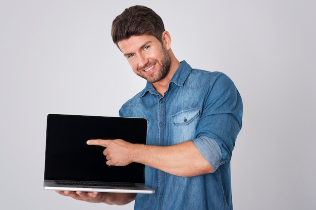 Homem posando com camisa jeans e laptop
