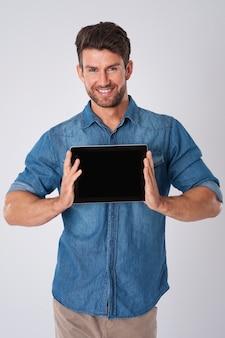 Homem posando com camisa jeans e tablet