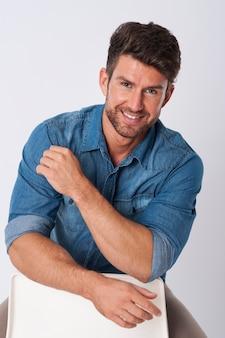 Homem posando com camisa jeans sentado em uma cadeira