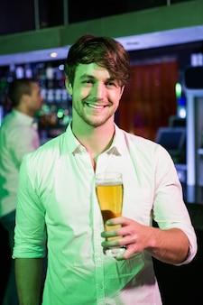 Homem posando com copo de cerveja e amigo no balcão de bar