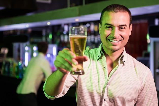 Homem posando com copo de cerveja e amigo no bar