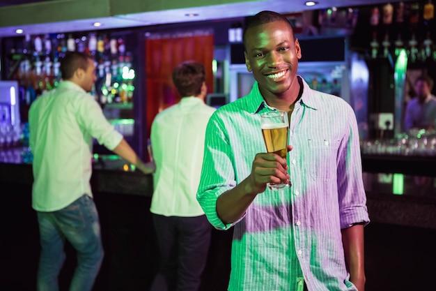 Homem posando com copo de cerveja e amigos no balcão de bar