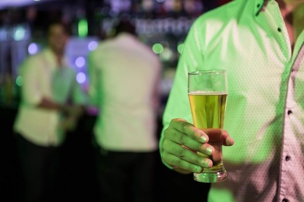 Homem posando com copo de cerveja em bar