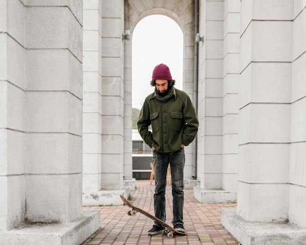 Homem posando com seu skate na cidade