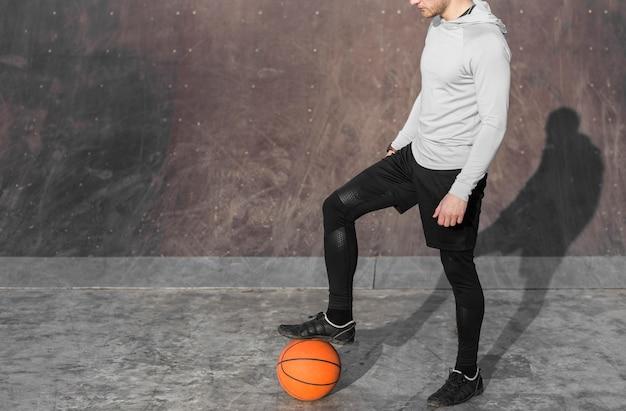 Homem posando com uma bola de basquete aos pés