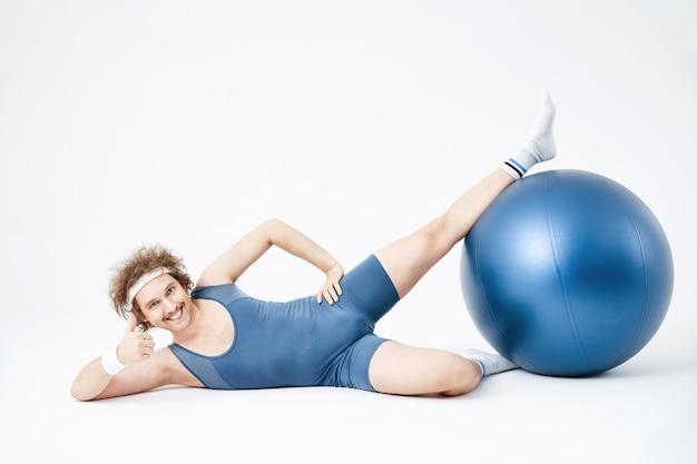 Homem posando deitado no chão, segurando uma bola de exercício com as pernas