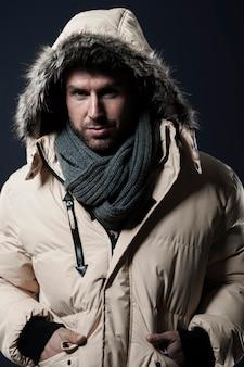 Homem posando e vestindo uma jaqueta de inverno