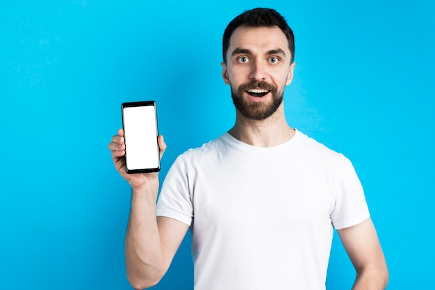 Homem posando enquanto segura o smartphone