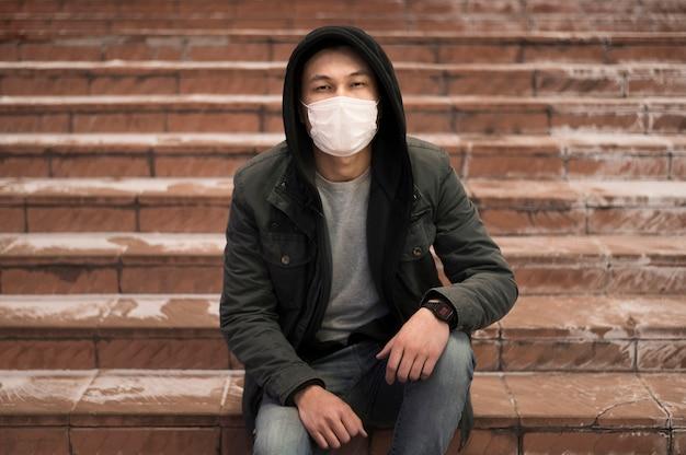 Homem posando na escada enquanto usava máscara médica