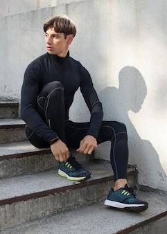 Homem posando na escada, vestindo roupas esportivas