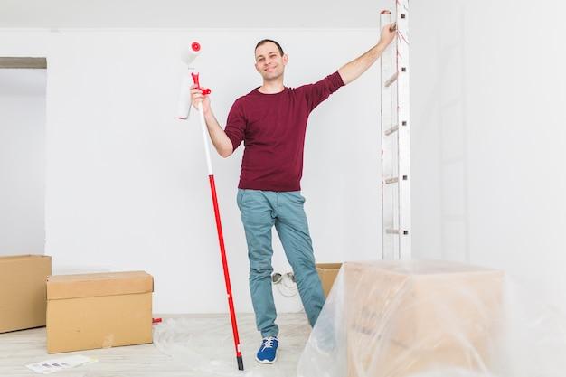 Homem, posar, com, escada, e, pintar rolo