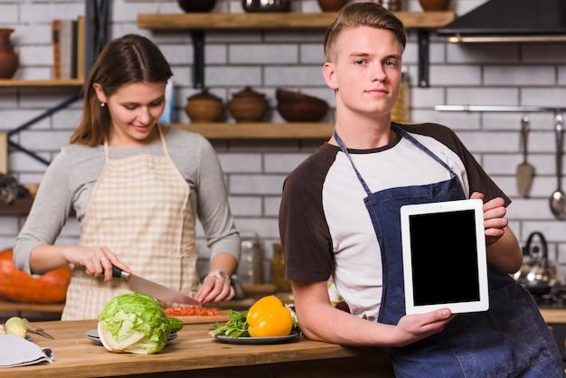 Homem, posar, com, tabuleta, enquanto, mulher, cozinhar