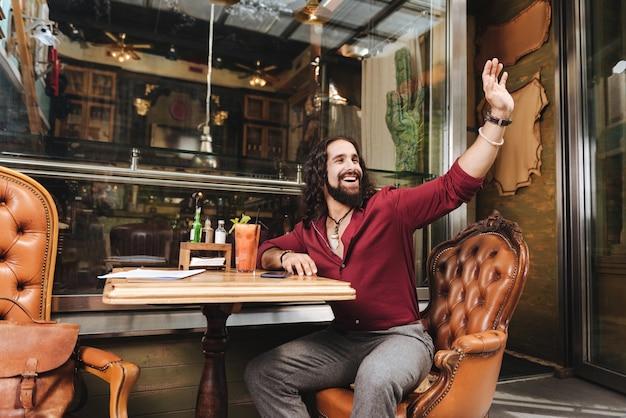Homem positivamente encantado sentado no refeitório enquanto pedia ao garçom para vir