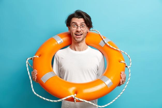 Homem positivamente surpreso posa com bóia salva-vidas inflada