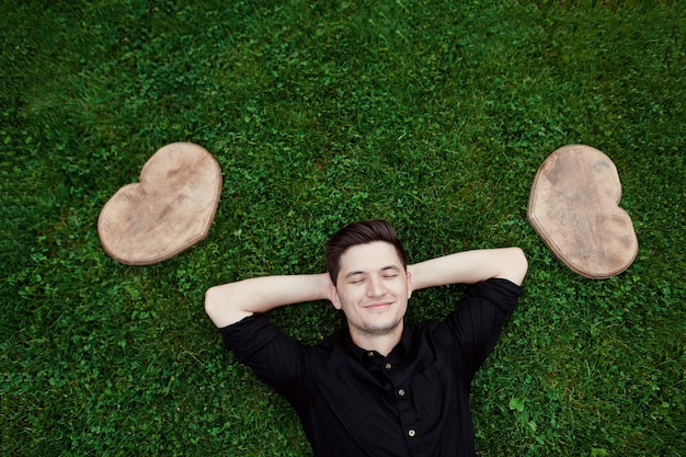Homem positivo aproveitando o dia de verão na grama entre dois corações de madeira