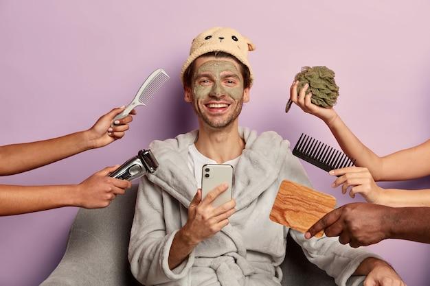 Homem positivo bem preparado usa roupão de banho, chapéu, usa smartphone depois de tomar banho
