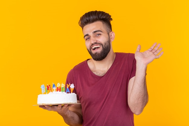 Homem positivo bonito jovem hippie em t-shirt cor de vinho segurando o bolo de felicitações com feliz aniversário de inscrição posando em uma parede amarela. conceito de parabéns e aniversários.