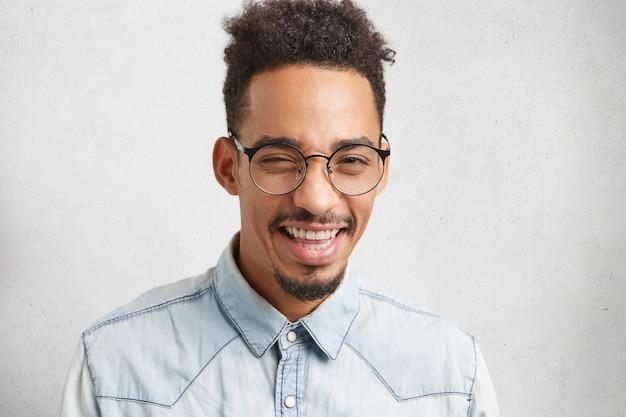 Homem positivo com barba e bigode pisca com os olhos, sorri ou sorri, tem bom humor após festa barulhenta com amigos.
