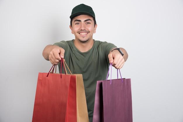 Homem positivo com sacolas de compras contra um fundo branco.