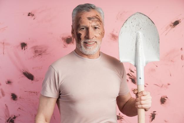 Homem positivo com uma pá na parede de uma parede rosa suja