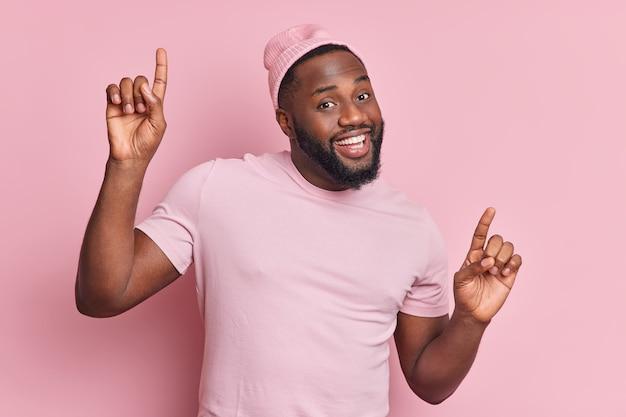 Homem positivo de pele escura com barba espessa dança despreocupado, levanta os braços, tem bom humor