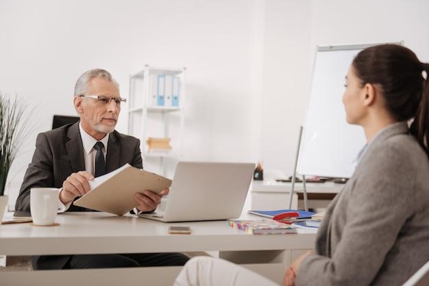 Homem positivo e encantado com um sorriso no rosto, segurando a pasta com as duas mãos, enquanto aprecia o trabalho no escritório