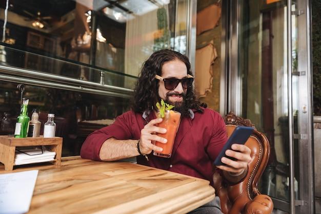 Homem positivo e feliz apreciando sua bebida enquanto relaxa no café