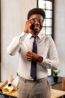 Homem positivo e feliz sorrindo enquanto tem uma conversa agradável ao telefone com seu cliente