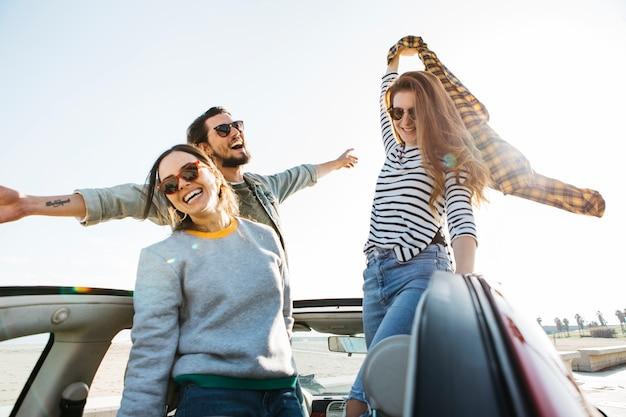 Homem positivo e sorrindo mulheres com saia na mão, se divertindo e inclinando-se para fora do carro