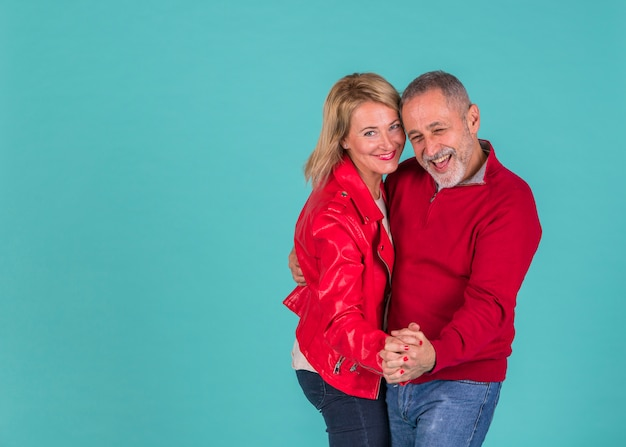 Homem positivo envelhecido dançando com mulher rindo