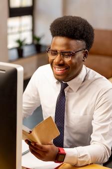 Homem positivo estando de bom humor enquanto termina um projeto de sucesso no trabalho