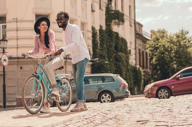 Homem positivo na rua, ajudando a mulher a andar de bicicleta. banner modelo