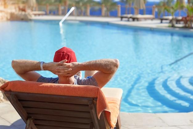 Homem positivo no chapéu vermelho que descansa perto do hotel da piscina em egito. estilo de vida bonito conceito