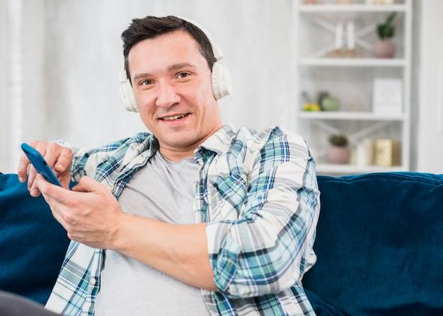 Homem positivo ouvindo música em fones de ouvido e navegando no smartphone no sofá