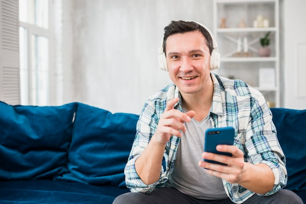 Homem positivo ouvindo música em fones de ouvido e segurando o smartphone no sofá
