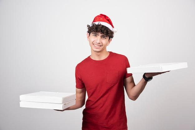 Homem positivo posando com caixas de pizza.