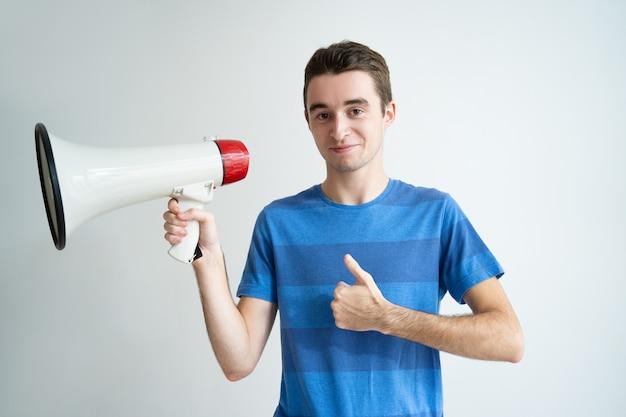 Homem positivo, segurando, megafone, e, mostrando, polegar cima