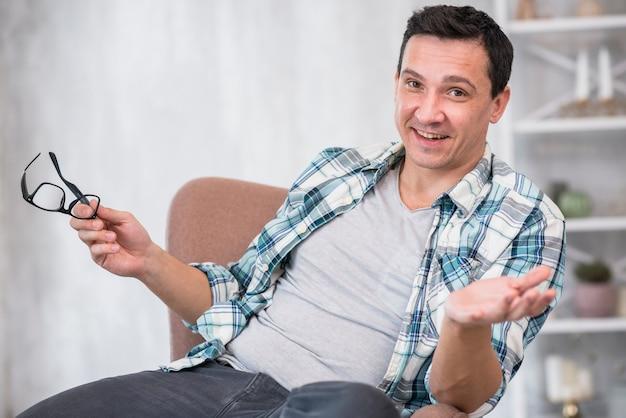 Homem positivo segurando óculos na cadeira em casa