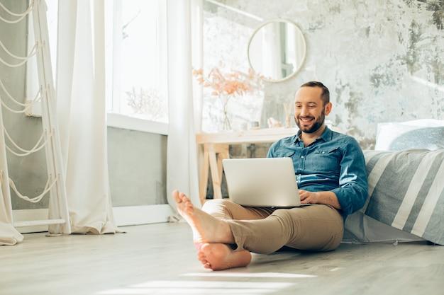 Homem positivo sentado no chão com os pés descalços no quarto e sorrindo enquanto trabalha no laptop