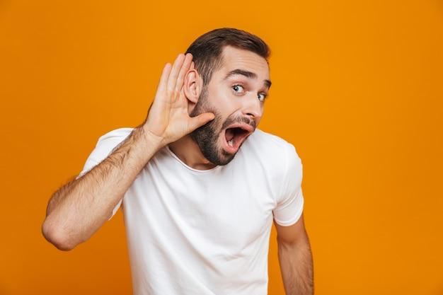 Homem positivo tentando ouvir algo enquanto mantém a mão em seu ouvido, isolado no amarelo
