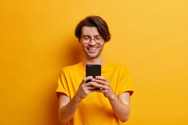 Homem positivo usa celular moderno para bater papo online