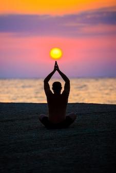 Homem pratica ioga na praia, o mar pela manhã, ao nascer do sol.