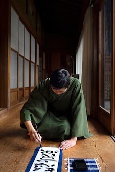 Homem praticando caligrafia japonesa com pincel e tinta