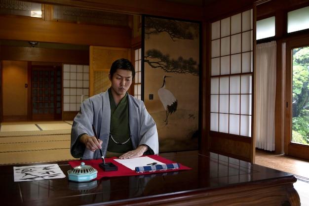 Homem praticando caligrafia japonesa com um pincel