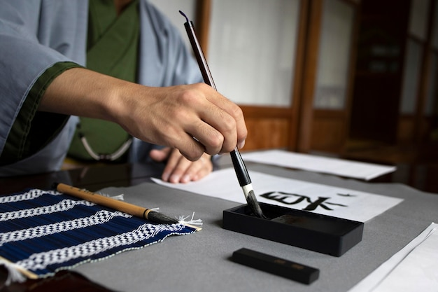 Homem praticando caligrafia japonesa com uma variedade de ferramentas